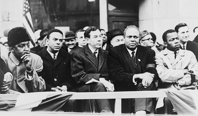 """John Lewis at far right, at the 1965 signing of the Voting Rights Act,. with Bayard Rustin, Andrew Young and James Farmer, who had also made """"good trouble"""" toward that day."""