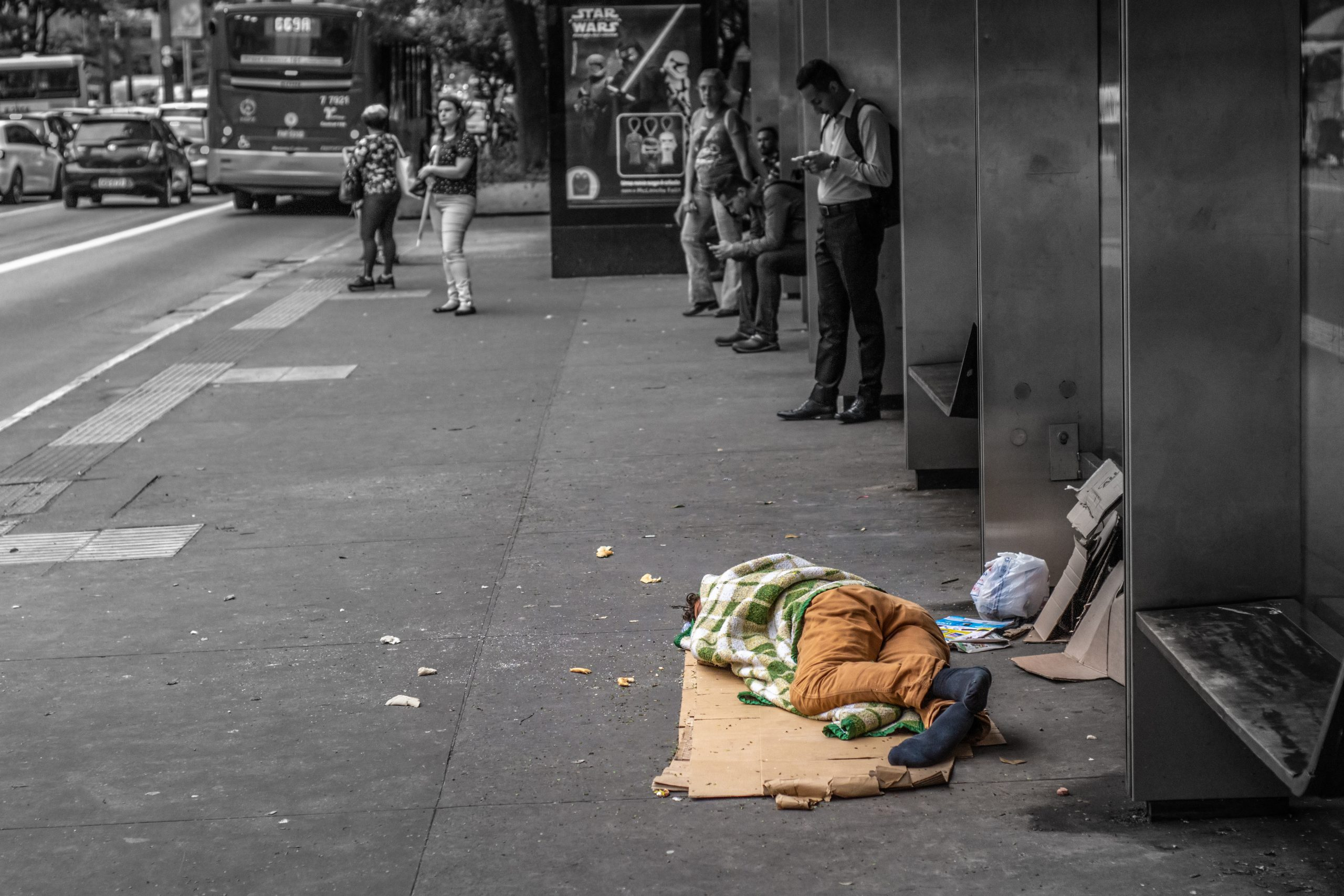 A homeless person sleeps on a piece of cardboard on the sidewalk. The image is largely black-and-white, with the homeless person appearing in color.