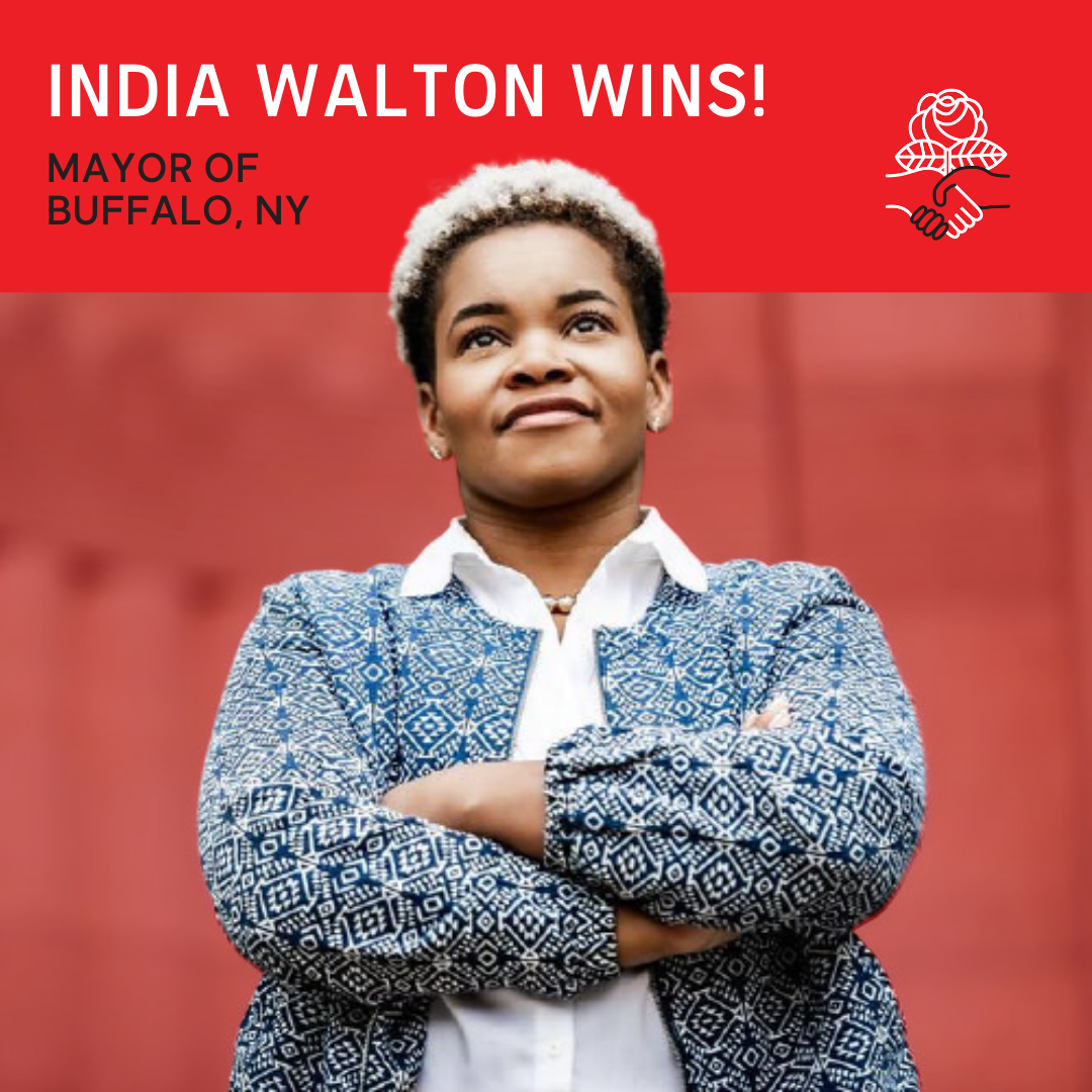 India Walton wins! Mayor of Buffalo, NY. Photo of India Walton, a Black woman, standing with her arms crossed and a can-do expression. She is smiling and looking up and forward towards the future. At right, the DSA logo of two hands shaking and a rose rising from them.