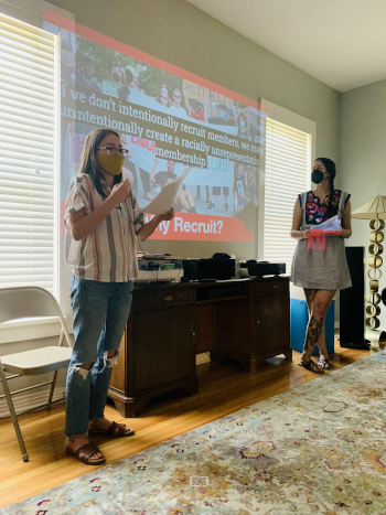 """Field organizer Amy Z with UTEP YDSA member teaching an all-day organizing workshop in El Paso, Texas. A presentation slide projected on the wall shows people marching with a banner. Slide says """"Why recruit? If we don't intentionally recruit members, we may unintentionally create a racially unrepresentative membership."""""""